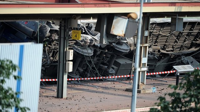 Carriages derailed in an accident lie within Bretigny-sur-Orge railway station