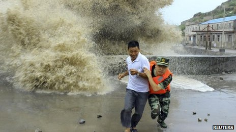 A frontier soldier helps a man move away from strong waves in Wenzhou, Zhejiang province, China, 13 July, 2013