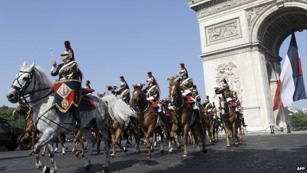 Republican Guard riders pass the Arc de Triomphe on the annual Bastille Day parade in Paris, 14 July 2013