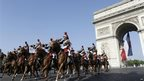 Republican Guard riders pass the Arch of Triumph on the Place de l'Etoile.