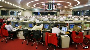 Floor traders study stock prices in the Hong Kong Stock Exchange