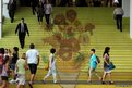 People walk on stairs featuring a five-metre-high reproduction of Vincent van Gogh's painting Sunflowers, at the entrance to Ocean Terminal in Hong Kong