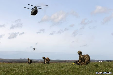 Helicopter flies above troops