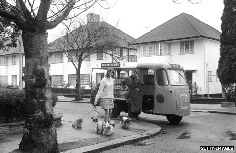 A milkman talks to a woman walking her dogs circa 1960s