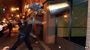 A man throws a trash can at the window of a building during a protest after George Zimmerman was found not guilty in the 2012 shooting death of teenager Trayvon Martin 14 July 2013