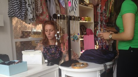 Woman sits behind a table at a boutique