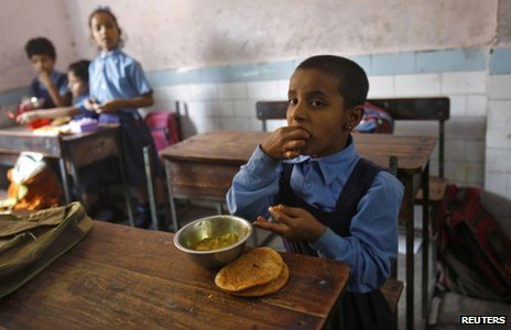 A schoolgirl eats her free mid-day meal, distributed by a government-run primary school, in New Delhi May 8, 2013