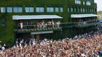 Andy Murray stands on the balcony to show the crowds the trophy