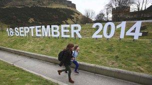 Children running alongside sign showing referendum date