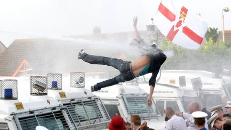 Protester knocked off Land Rover by water cannon