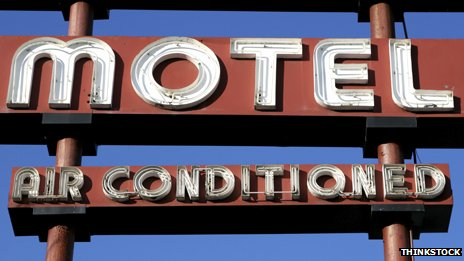 "A motel sign saying ""Air conditioned"" below"
