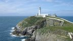 A white lighthouse and building to the side of it sit on a green and rocky headland. Sea and blue sky surround it.