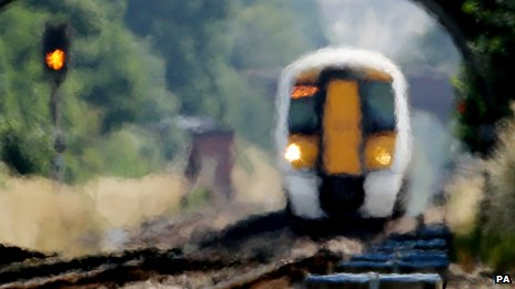 An approaching train looks blurred through the heat haze