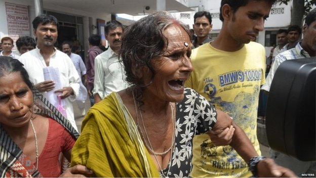 A crying woman is escorted after her grandson died at a hospital in the city of Patna on 17 July 2013