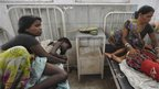 Two women sit with their sick children in a hospital in Patna on 17 July 2013