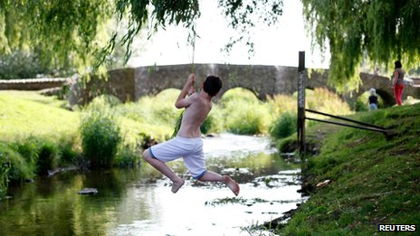 A boy swings across a stream in Anstey, England