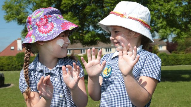 Children with sun cream and hats on.