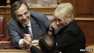 PM Antonis Samaras is congratulated by MPs after the vote