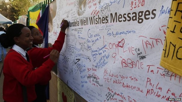 Well-wishers write messages of support outside the hospital where Nelson Mandela is being treated in Pretoria, South Africa, 17 July 2013