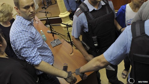 Russian protest leader Alexei Navalny (L) is handcuffed and escorted by Interior Ministry officers in a courtroom in Kirov, July 18, 2013