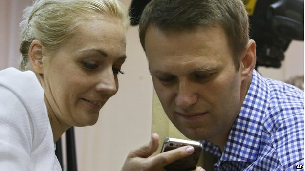 Russian opposition leader Alexei Navalny and his wife Yulia look at a mobile phone during the trial in Kirov, Russia, Thursday, July 18, 2013.