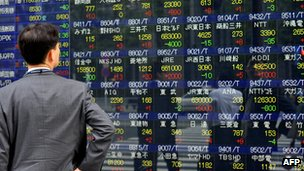 An investor looking at a stock market board in Japan