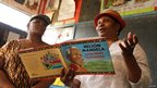 Two women read from a children's version of Nelson Mandela's autobiography to a school class in Nairobi (18 July)