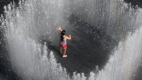 A girl plays in the Appearing Rooms fountain, by Danish artist Jeppe Hein, on London's Southbank