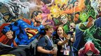 Fans posing in front of a comic mural.
