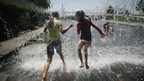 Angela Bradbury, 11, left, and Zoe Riedel, 8, right, jump through a waterfall to cool-off at the Yards Park, near the Washington Nationals baseball stadium, where temperatures were in the mid-90s 16 July 2013