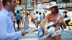 The Naked Cowboy performs in the midday heat in Times Square in New York City on 16 July 2013