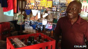 Shopkeeper with crate of soft drinks and medications