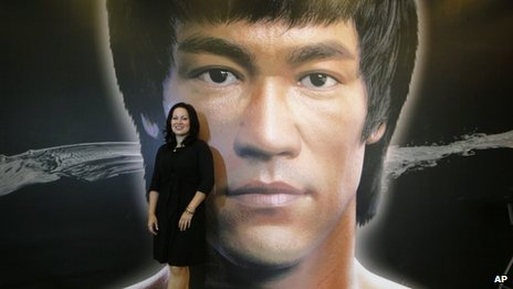 "Shannon Lee, daughter of the late Kung Fu star Bruce Lee, poses in front of a promotional poster for Lee""s memorial exhibition at the Hong Kong Heritage Museum Thursday, July 18, 2013,"