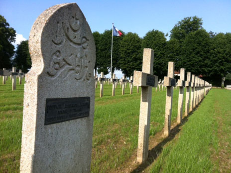 Muslim tombstone in a row of crosses