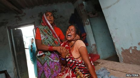 A woman mourns the death of her niece, who died after eating a contaminated meal at a school on Tuesday in Bihar's Chhapra district on 18 July 2013