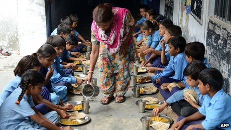 Indian schoolchildren eat their free mid-day meal at a government school in Amritsar on July 19, 2013