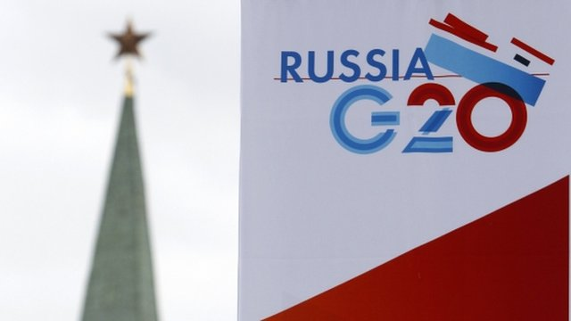 A tower of the Kremlin is seen behind a sign hanging on the Manezh Exhibition Center, venue for this week's meeting of G20 Finance Ministers
