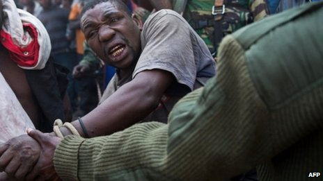A man accused by the Congolese army of being a spy of rebels of the M23 movement is tied and taken away on 16 July 2013 in Munigi on the outskirts of Goma in the east of the Democratic Republic of the Congo