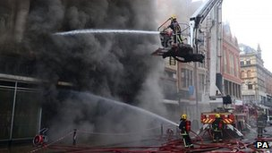 Fire fighters tackle the blaze at Paul's Hair World on Saturday