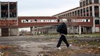 A person walks past the remains of the Packard Motor Car Company building in Detroit, November 2008