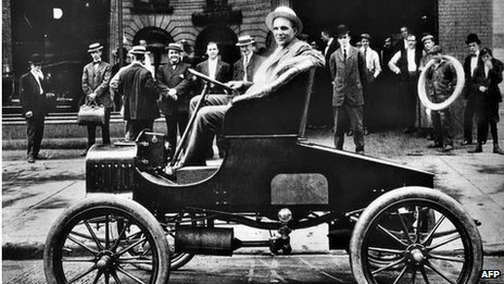 Henry Ford, US car manufacturer, poses in his new T Ford model in front of his car plant in Detroit in the early 1900s