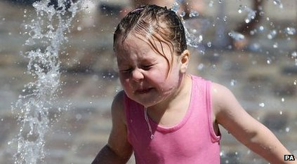 Girl plays in a water fountain