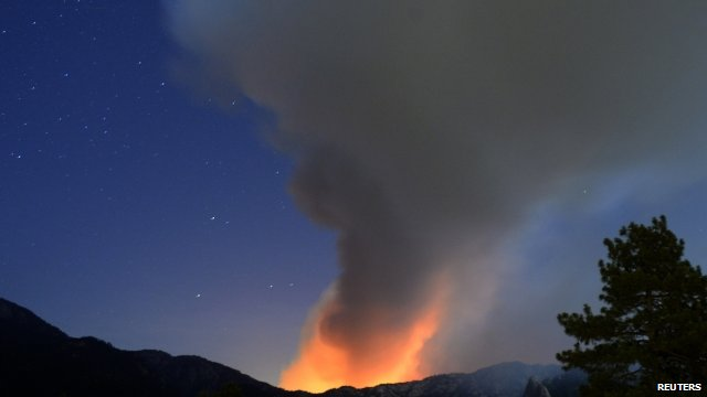 A plume of smoke rises into the night sky in southern California