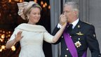 King Philippe kisses the hand of his wife Queen Mathilde as they greet crowds from the balcony of the Royal Palace in Brussels, 21 July 2013