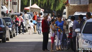 People stand outside their homes after a 6.6 magnitude earthquake hit Dingxi, Gansu province, 22 July 2013