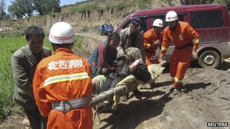 Firefighters carry an injured woman on a stretcher after a 6.6 magnitude earthquake hit Minxian county, Dingxi, Gansu province 22 July 2013
