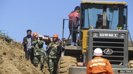A victim is carried out on a stretcher next to an excavator after a 6.6 magnitude earthquake hit Minxian county, Dingxi, Gansu province 22 July 2013