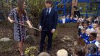 The Duchess of Cambridge plants a willow tree with comedian John Bishop during her visit to The Willows Primary School, Wythenshawe, Manchester, on 23 April, 2013