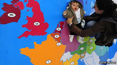A mother holds a baby over a floor map of Europe