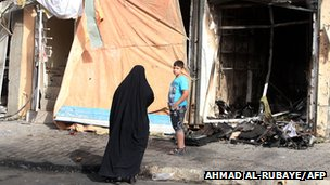 Iraqis look at destroyed shops following a car bomb in the Topchi neighbourhood of northern Baghdad (July 21, 2013)